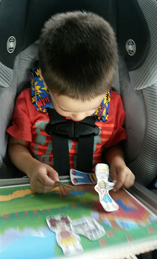 Boy playing with Billy Gorilly magnetic activity board in the car